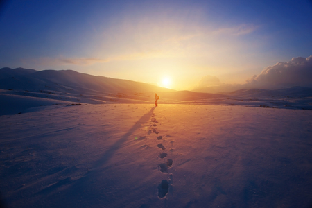 person: Lonely woman standing far away in bright yellow sunset light, traveling with backpack in the mountains covered with snow