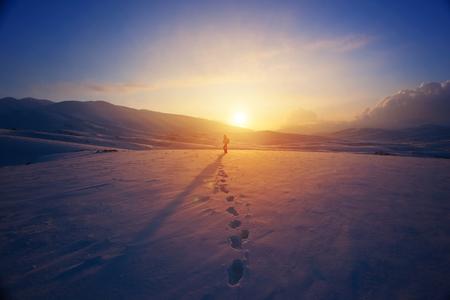 persona de pie: Mujer sola que se coloca muy lejos, en la luz brillante puesta de sol de color amarillo, que viajan con mochila en las monta�as cubiertas de nieve Foto de archivo