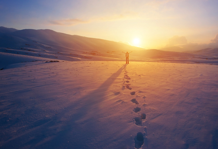 Gelukkig blije vrouw plezier buitenshuis in de winter, staande op de bergen met opgewekt handen op de berg bedekt met sneeuw, genieten van prachtige zonsondergang