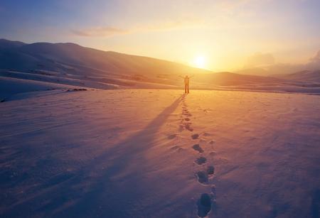 Mujer alegre feliz divertirse al aire libre en invierno, de pie en las montañas con levantado las manos en la montaña cubierta de nieve, disfrutando de hermosa puesta de sol