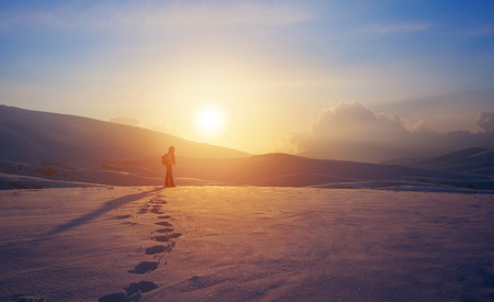 winter escape: Lonely woman standing far away in bright yellow sunset light, traveling with backpack in the mountains covered with snow