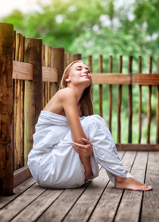 closing eyes: Sensual woman on spa resort, sitting on the floor of outdoors veranda wrapped in bed sheet, dreamy closing eyes and enjoying silence and harmony