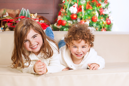 christmas spending: Two happy kids lying down on sofa under beautiful decorated Christmas tree and laughing, cheerful family spending winter holidays at home