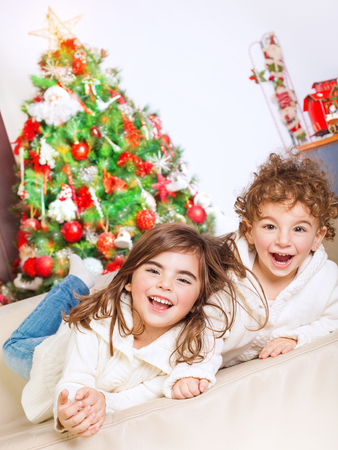christmas spending: Two happy kids lying down on sofa near beautiful decorated Christmas tree and laughing, cheerful family spending winter holidays at home Stock Photo