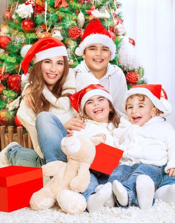 familia abrazo: Retrato de la hermosa familia feliz que se sienta cerca hermoso árbol de Navidad decorado en casa, vistiendo sombreros rojos de Santa, la celebración de las vacaciones de invierno