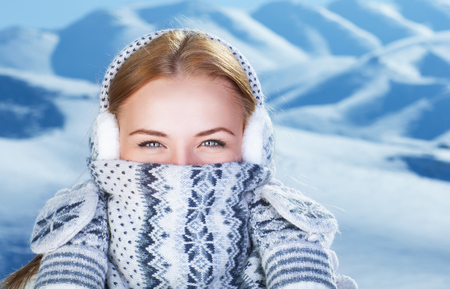 snow covered mountain: Closeup portrait of happy cute woman standing outdoors and covering face with beautiful warm knitted scarf, spending winter holidays in the snowy mountains Stock Photo