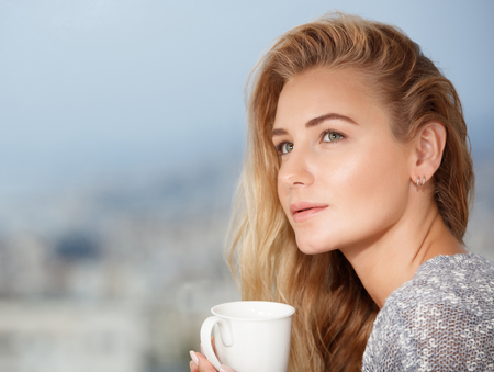 relaxation: Portrait of a nice calm blond female drinking tea on the outdoors terrace, having breakfast at home, feeling morning pleasure and relaxation