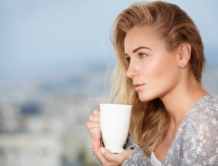 hot drink: Portrait of cute blond female drinking tea on the outdoors terrace, having breakfast at home, feeling pleasure and relaxation Stock Photo