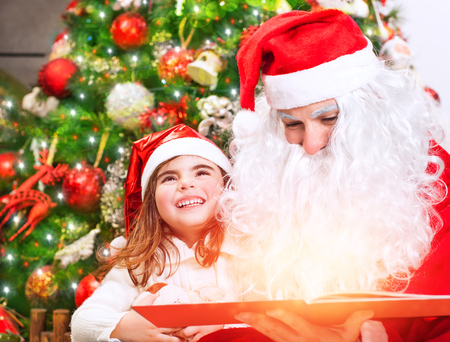 christmas story: Portrait of little charming baby girl with Santa Claus reading magical Christmas story, enjoying wonderful festive fairy tale