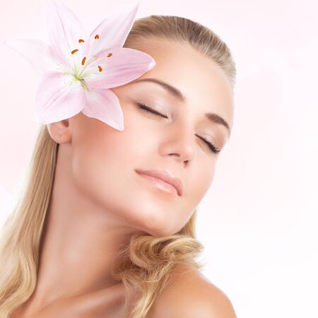 nude female body model: Closeup portrait of gentle cute female with pink lily flower in hair isolated on white background, closing eyes of pleasure in day spa