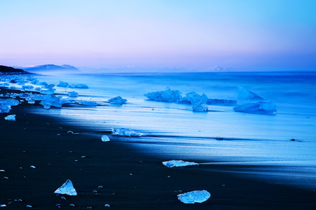 Iceberg on the black sand beach, melting glacier on the shore of North Atlantic Ocean, stunning scandinavia, landscape of North Pole, Vatnajokull National Park, Jokulsarlon landmark, Iceland
