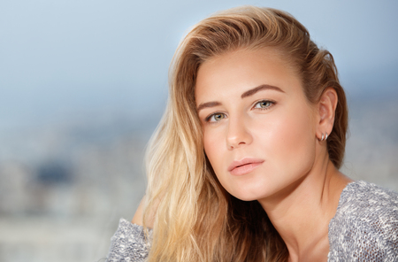outdoor photo: Closeup portrait of beautiful blond woman outdoors over soft focus background, healthy natural beauty