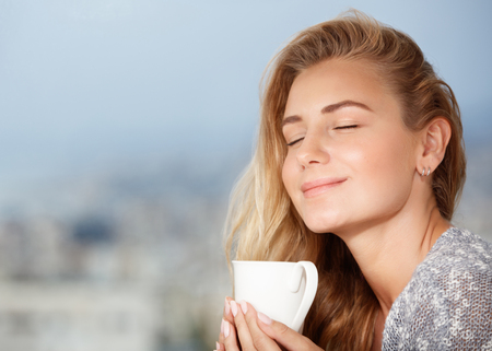 Portrait of beautiful happy girl with closed eyes, enjoying tasty strong morning coffee aroma, having breakfast in outdoor cafe Banco de Imagens