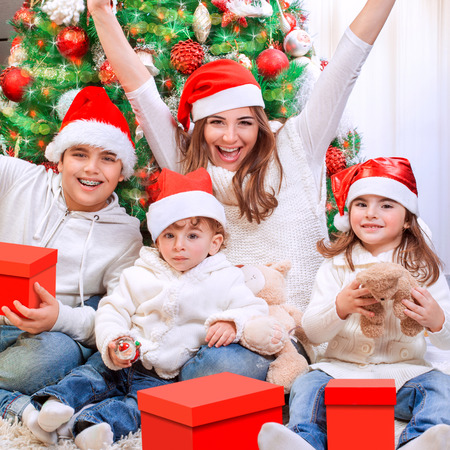 man hat: Portrait of happy mother with three cheerful kids enjoying gifts receiving from Santa Claus, having fun near Christmas tree