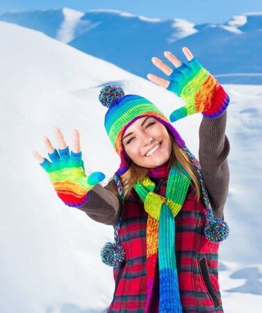 people and nature: Portrait of cute smiling girl waving hands, wearing stylish colorful outfit, spending active winter holidays in the snowy mountains