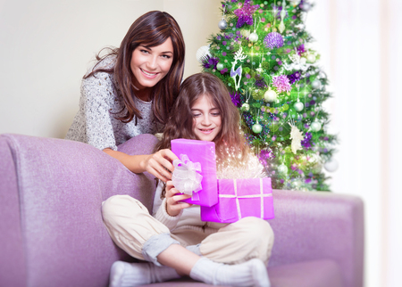 gift spending: Cute teen girl receive gift from her beautiful young mother, happy family enjoying magical glowing present, spending Christmas holidays at home
