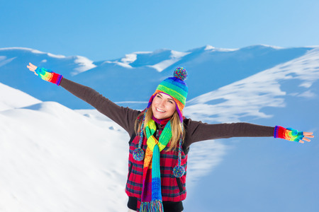 weather: Happy joyful woman with raised hands enjoying beauty of winter nature, spending leisure time in the snowy mountains