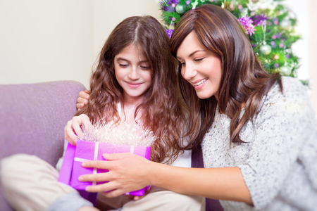 baby open present: Portrait of beautiful mother with cute daughter with pleasure opening gift box, receiving magical glowing present, wonderful surprise on Christmas eve Stock Photo