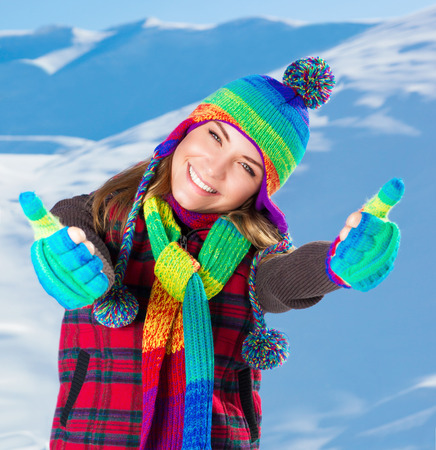 good mood: Portrait of cute smiling girl gesturing by hands good mood, wearing stylish colorful outfit, spending active winter holidays in the snowy mountains Stock Photo