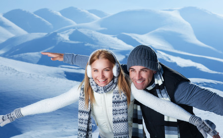 winter couple: Happy couple playing outdoors in winter, imitate the flight by hands, having fun together in the snowy mountains, with pleasure spending Christmas holidays Stock Photo