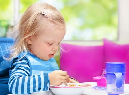 niños desayunando: Niña linda rubia bebé sentado en la cocina en casa y tener el desayuno, la nutrición del niño sano, feliz infancia despreocupada