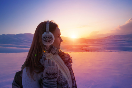 earmuff: Side view of beautiful girl enjoying amazing view on sunset, spending winter holidays in the snowy mountains, active lifestyle of young people
