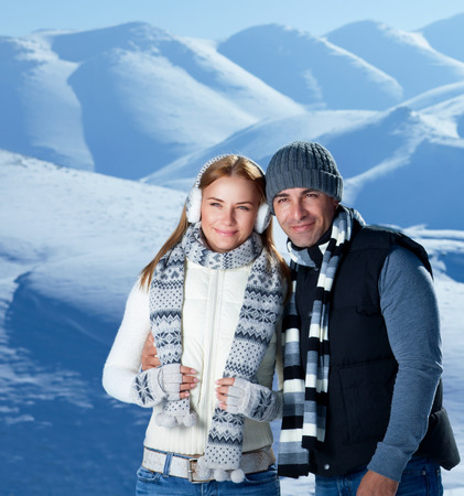 young happy couple: Happy active couple spending winter holidays in the mountains covered with snow, young family with pleasure travel together