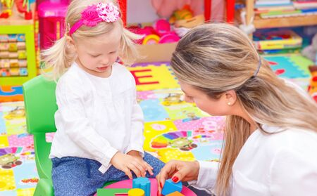 game time: Cute little girl with young beautiful mother playing game in colorful playroom, happy family with pleasure spending time together