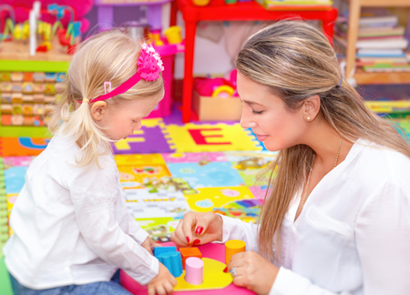 communicating: Cute little girl with young beautiful mother playing game in colorful playroom, happy family with pleasure spending time together
