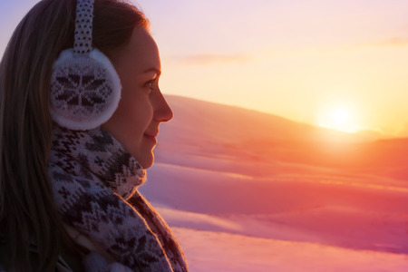 view to outside: Closeup portrait of side view woman enjoying beautiful sunset over mountains covered with snow, winter tourism, active healthy lifestyle Stock Photo