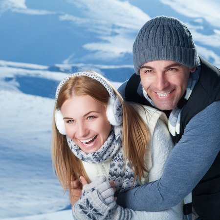 laughing girl: Closeup portrait of cheerful smiling couple playing with each other in the winter park, having fun in the mountains, happy wintertime holidays Stock Photo
