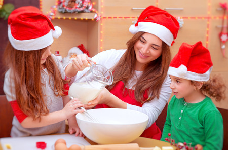 christmas cooking: Mother with two cute kids baking on the kitchen at home, wearing red Santa hat, making traditional Christmas preparation