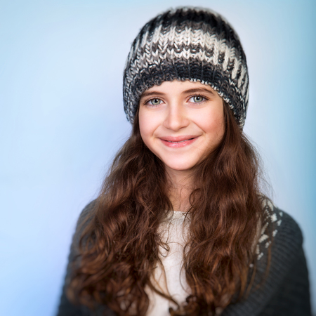white girl: Portrait of cute teen girl wearing stylish knitted hat and sweater isolated on blue background, winter fashion for teenagers