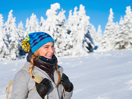 Happy woman on winter holidays in the snowy mountains, trekking with backpack along Alps, healthy active lifestyle Stockfoto