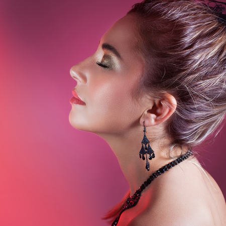 makeup eyes: Side view portrait of gorgeous female with closed eyes over pink background, wearing elegant earrings and necklace, fashion look for Christmas party