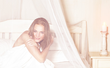 Portrait of gentle romantic woman sitting in the bed under gentle transparent valance, spending weekend in luxury spa hotel, enjoying rest and relaxation Stock Photo
