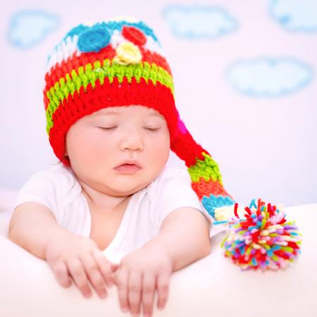 ojos cerrados: Retrato de Linda ni�a dulce con los ojos cerrados de relax en el sof� de casa, vestido con sombrero divertido colorido de punto