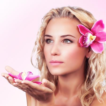 junge nackte m�dchen: Nahaufnahmeportrait des netten sanfte Frau mit Orchidee Blume �ber rosa Hintergrund, genie�en Aromatherapie und nat�rliche Sch�nheitsbehandlung