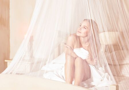 Gentle girl enjoying wonderful day in luxury spa hotel, sitting on the bed under white transparent net and dreamy looking in side