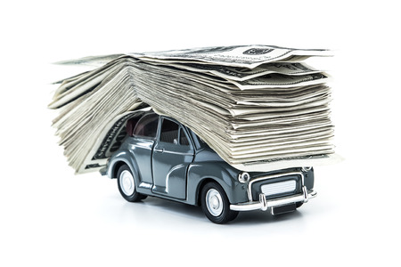 white car: Small decorative car model carries on itself a lot of cash isolated on white background, dollars of USA, credit for car concept Stock Photo