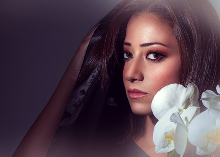 Closeup portrait of gorgeous brunette woman with white orchid flowers over dark background, luxury beauty salon photo