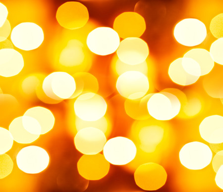 Golden festive background, beautiful blurry glowing yellow lights, New Year greeting card, shiny Christmas wallpaper Stock Photo