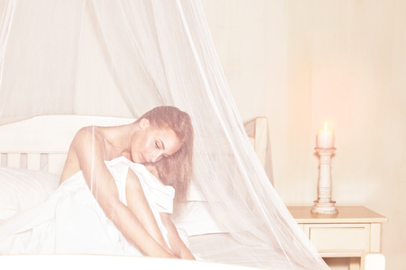 day bed: Gentle girl enjoying wonderful day in luxury spa hotel, sitting on the bed under white transparent net and thoughtful looking down Stock Photo