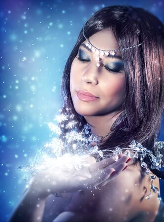 glowing: Portrait of beautiful princess looking on magical glowing light on her hand, Christmas miracle, fashion look for winter holidays