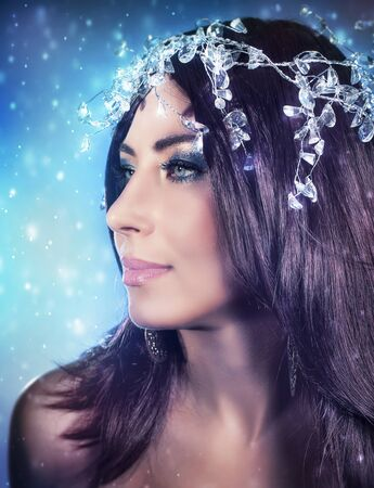 winter fashion: Closeup portrait of beautiful woman with perfect evening makeup wearing gorgeous diamonds wreath over blue snowy background Stock Photo