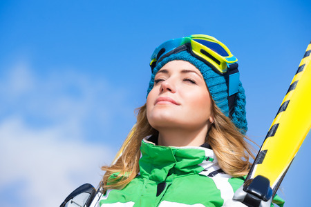 pretty eyes: Portrait of pretty female with closed eyes enjoying winter nature over blue sky background, relaxing on ski resort Stock Photo