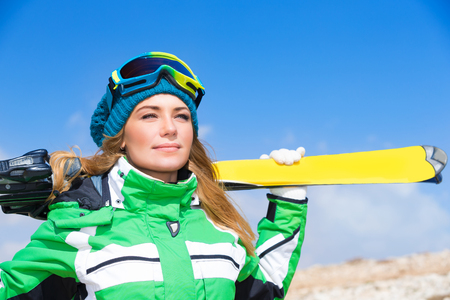 ski mask: Portrait of beautiful gorgeous skier woman, wearing sportive clothes and holding in hands ski, active wintertime vacation Stock Photo