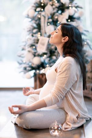 paz interior: Mujer embarazada meditando en su casa cerca hermoso árbol de Navidad decorado, sentado en posición de loto con los ojos cerrados, el cuidado del cuerpo y la paz interior