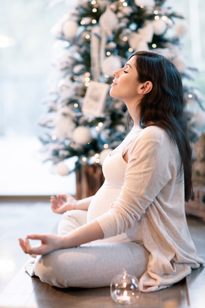 inner peace: Pregnant woman meditating at home near beautiful decorated Christmas tree, sitting in lotus pose with closed eyes, body care and inner peace
