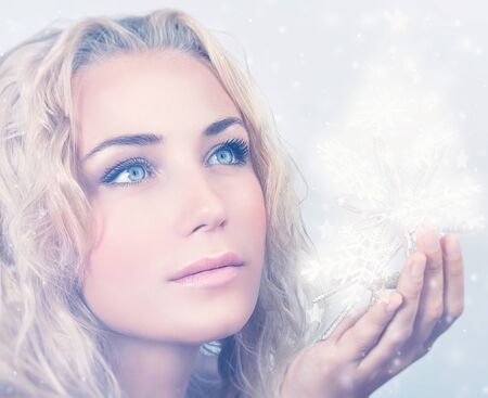 elegant girl: Closeup portrait of beautiful blond woman holding in hand magical glowing snowflakes, gorgeous snow queen, Christmas miracle